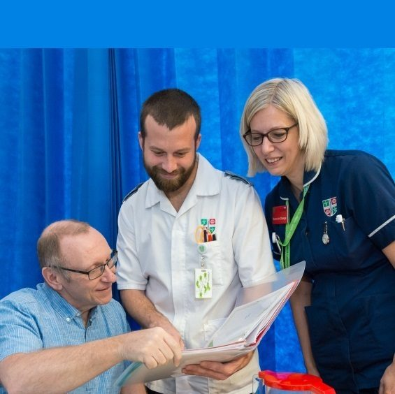 Male nurse, female sister and patient reading through documents