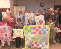 Group of WI ladies holding quilted blankets